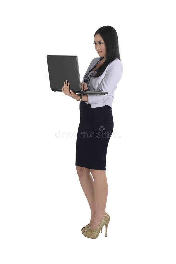 Mujer de negocios asiática sonriente que mecanografía mientras que sostiene el ordenador portátil imagen de archivo