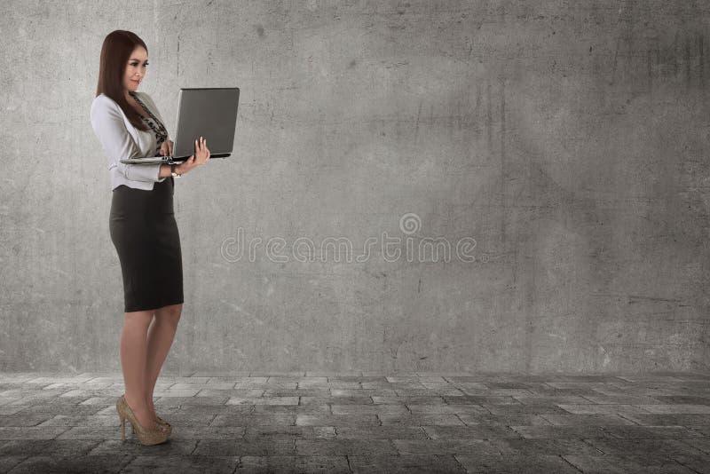 Mujer de negocios asiática sonriente que mecanografía mientras que sostiene el ordenador portátil fotografía de archivo