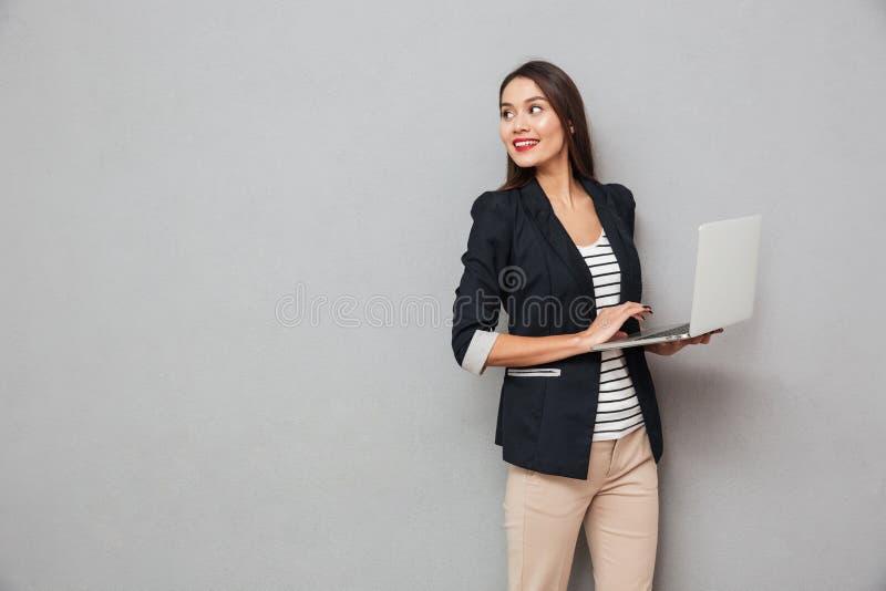 Mujer de negocios asiática sonriente que sostiene el ordenador portátil y que mira detrás fotografía de archivo