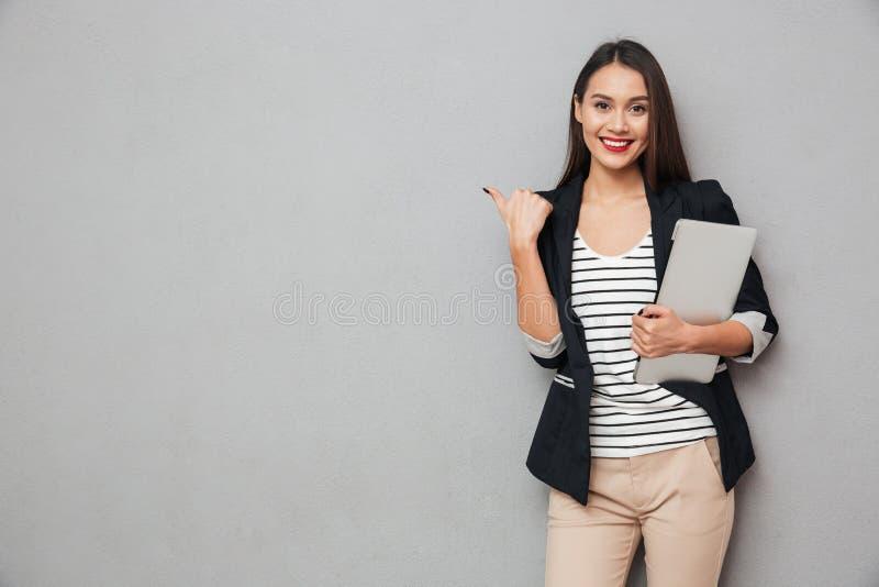 Mujer de negocios asiática sonriente que sostiene el ordenador portátil y que señala lejos imagenes de archivo