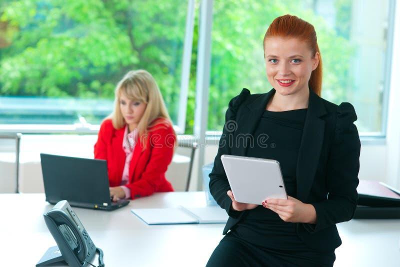 Mujer de negocios atractiva en oficina con la tableta fotos de archivo