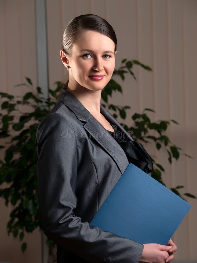 Mujer de negocios atractiva joven con la carpeta fotografía de archivo
