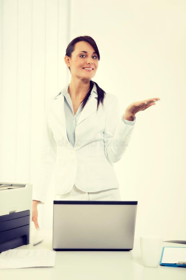 Mujer de negocios atractiva joven en la chaqueta blanca que muestra el espacio de la copia sobre fondo El gesticular de la mujer foto de archivo