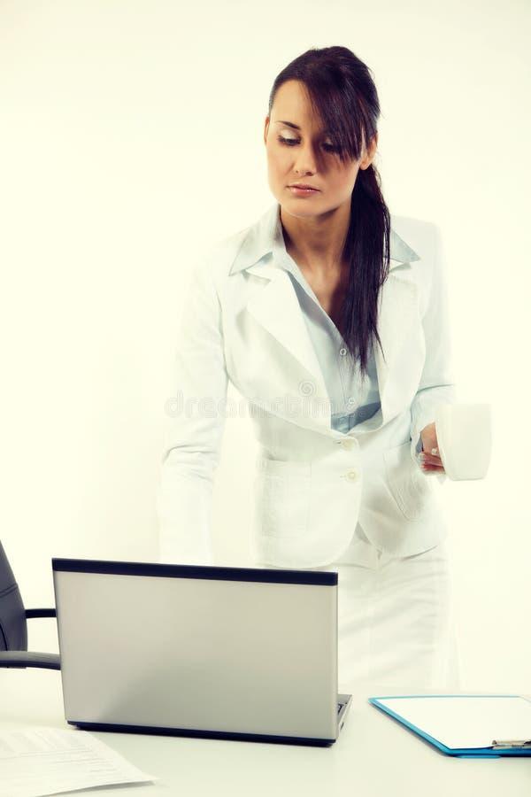 Mujer de negocios atractiva joven que usa el ordenador portátil en la oficina imagen de archivo