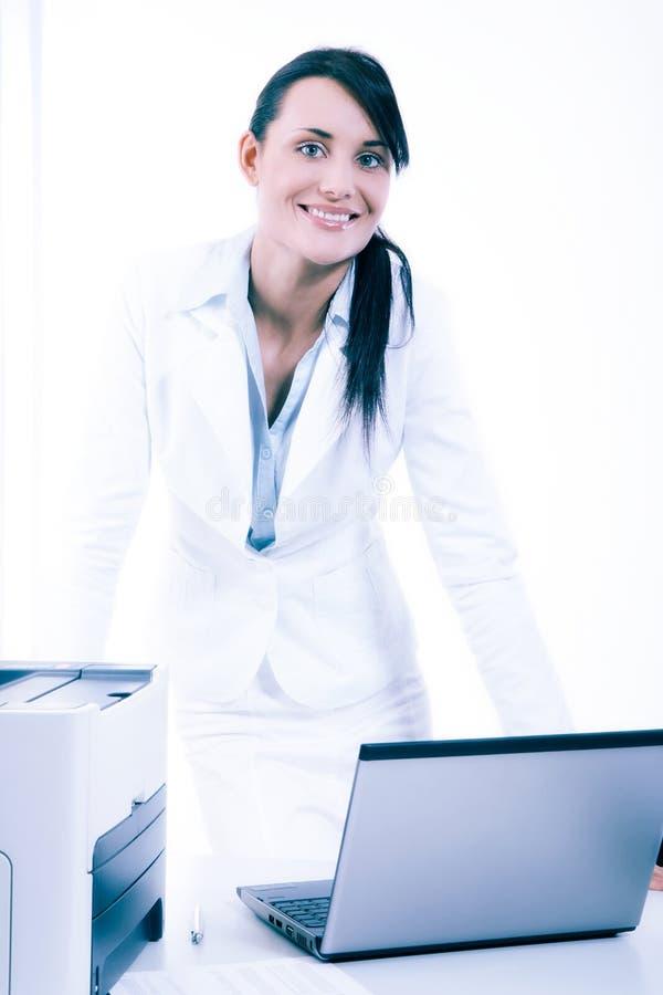 Mujer de negocios atractiva joven que usa el ordenador portátil en la oficina imagenes de archivo