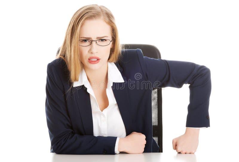 Mujer de negocios atractiva por la tabla, comportamiento mandón. imagenes de archivo