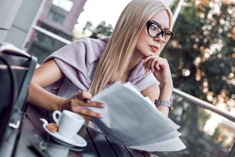 Mujer de negocios atractiva que lee los periódicos en el café de la ciudad fotografía de archivo