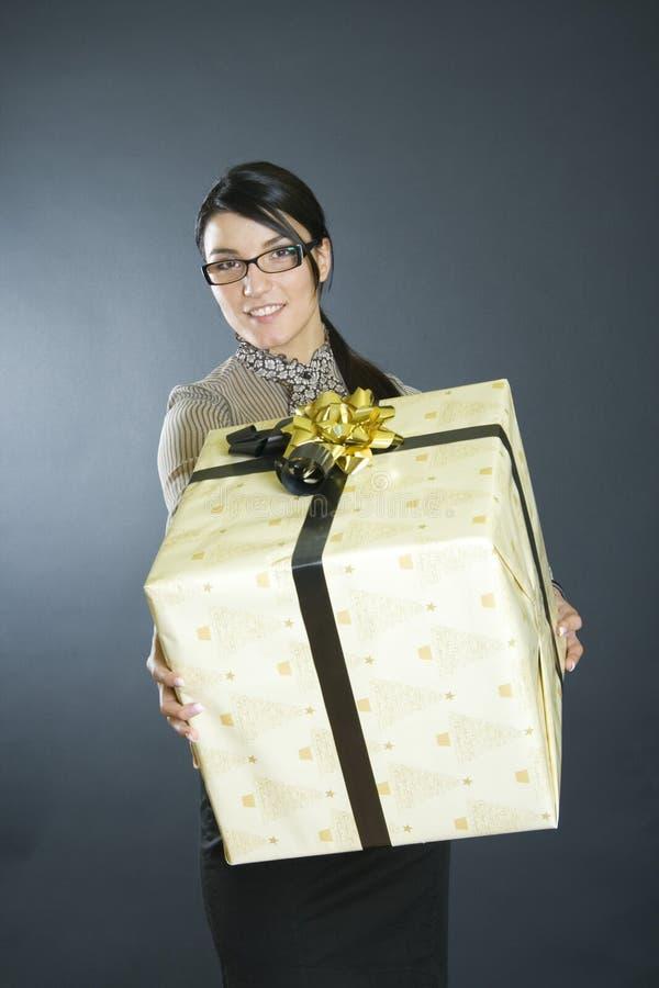 Mujer de negocios atractiva que ofrece un presente imagenes de archivo