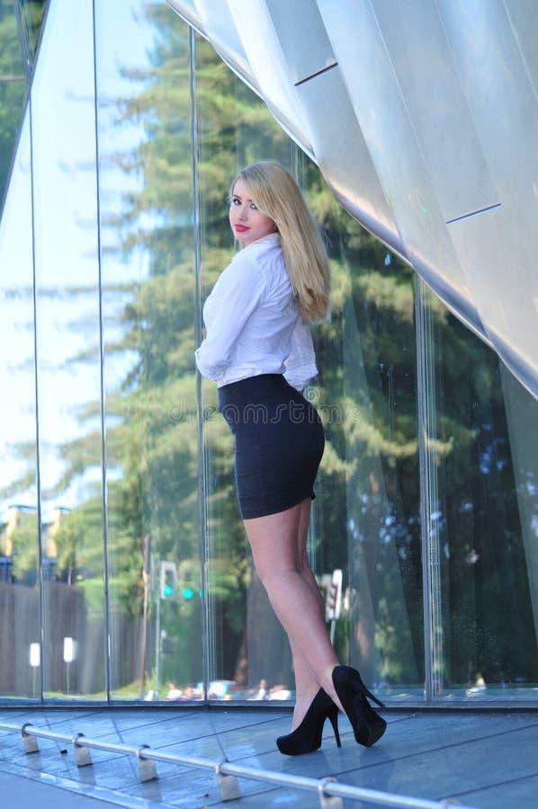Mujer de negocios atractiva que se coloca delante del edificio de oficinas fotografía de archivo