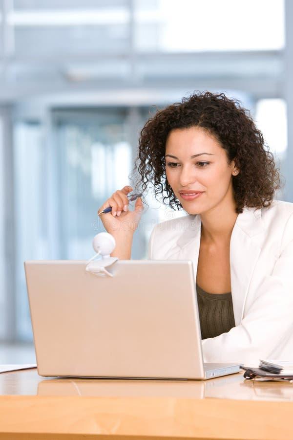 Mujer de negocios atractiva que trabaja en la computadora portátil imagen de archivo libre de regalías