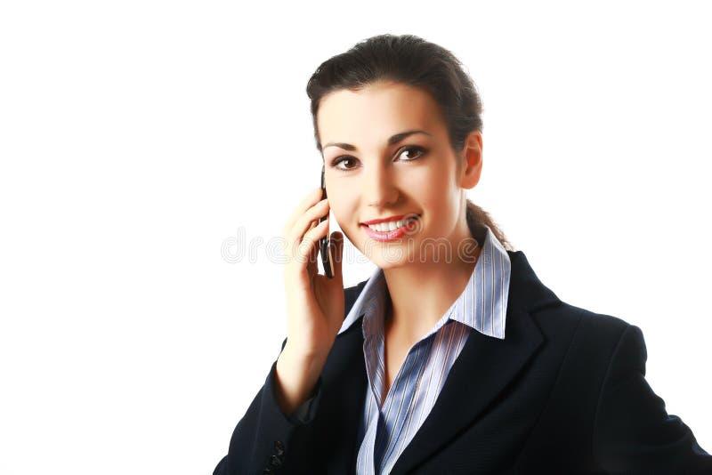Mujer de negocios atractiva sonriente que llama por el teléfono imagenes de archivo