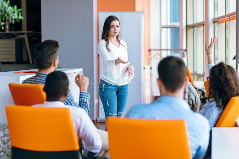 Mujer de negocios bastante joven que da una presentación en conferencia o que hace frente al ajuste fotos de archivo