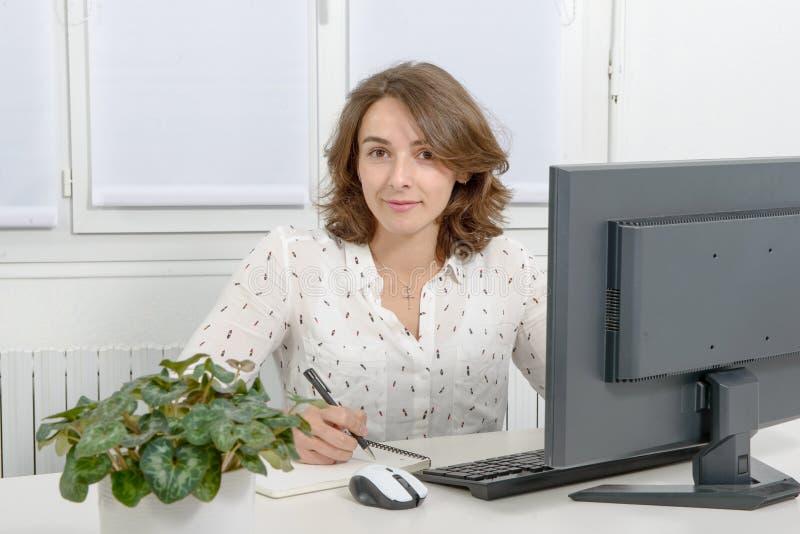 Mujer de negocios bastante joven que trabaja en la PC en oficina fotos de archivo libres de regalías