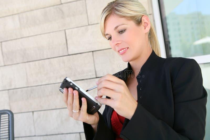 Mujer de negocios bastante rubia y PDA imagenes de archivo