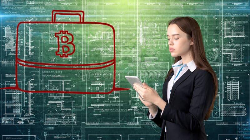 Mujer de negocios de Bauty que se coloca en traje con el logotipo de Bitcoin para ilustrar el uso del bitcoin para negociar o la  imagen de archivo