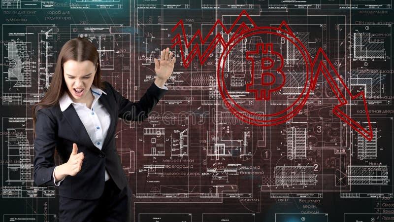 Mujer de negocios de Bauty que se coloca en traje con el logotipo de Bitcoin para ilustrar el uso del bitcoin para negociar o la  fotos de archivo