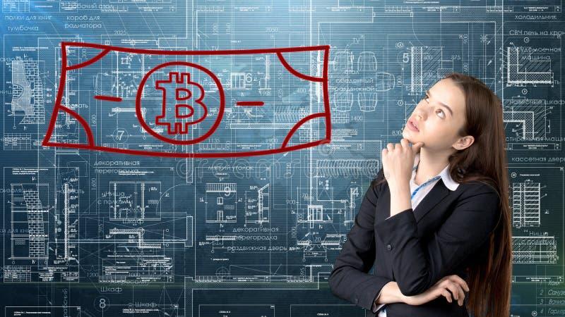 Mujer de negocios de Bauty que se coloca en traje con el logotipo de Bitcoin para ilustrar el uso del bitcoin para negociar o la  foto de archivo