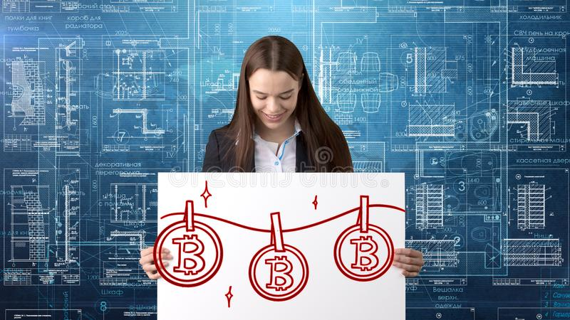 Mujer de negocios de Bauty que se coloca en traje con el logotipo de Bitcoin para ilustrar el uso del bitcoin para negociar o la  imagenes de archivo