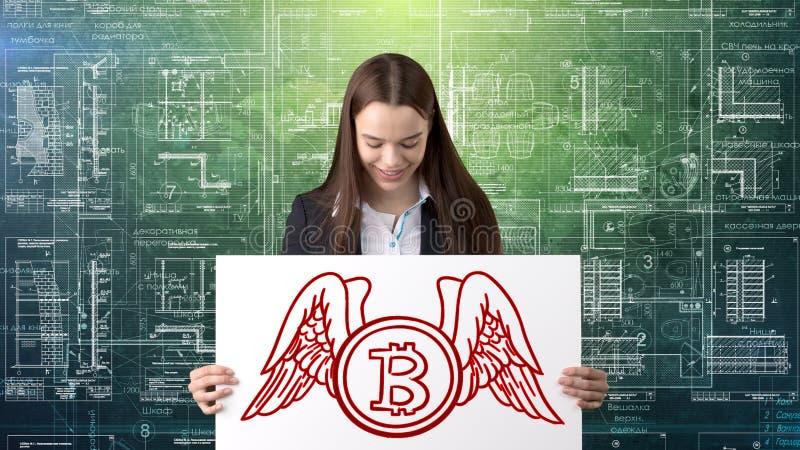 Mujer de negocios de Bauty que se coloca en traje con el logotipo de Bitcoin para ilustrar el uso del bitcoin para negociar o la  imágenes de archivo libres de regalías