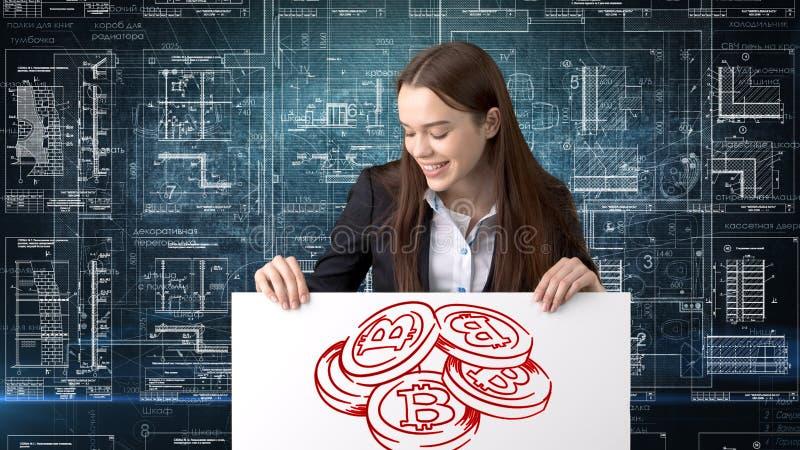 Mujer de negocios de Bauty que se coloca en traje con el logotipo de Bitcoin para ilustrar el uso del bitcoin para negociar o la  imagen de archivo libre de regalías