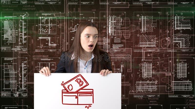 Mujer de negocios de Bauty que se coloca en traje con el logotipo de Bitcoin para ilustrar el uso del bitcoin para negociar o la  fotografía de archivo