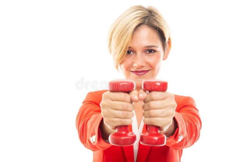 Mujer de negocios bonita joven que lleva a cabo pesas de gimnasia rojas fotos de archivo