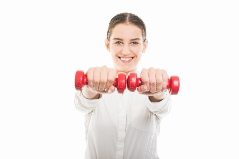 Mujer de negocios bonita joven que se resuelve con pesas de gimnasia imágenes de archivo libres de regalías