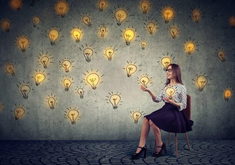 Mujer de negocios bonita que hace juegos malabares con las bombillas imagen de archivo
