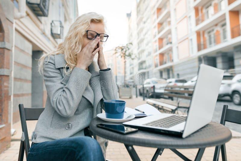 Mujer de negocios cansada con el ordenador portátil en café al aire libre, mujer que toca sus ojos con sus vidrios apagado, fondo fotos de archivo