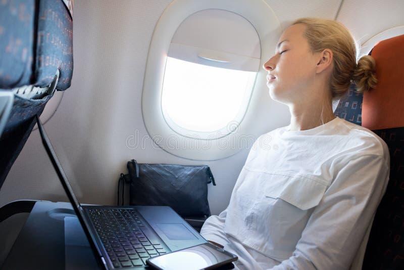 Mujer de negocios cansada que toma una siesta en el aeroplano durante sus tareas woking del viaje de negocios imagen de archivo libre de regalías