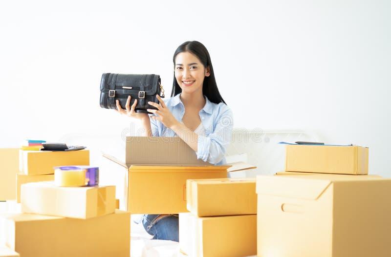 Mujer de negocios casual joven que trabaja el holdin en línea de la pequeña empresa imagenes de archivo