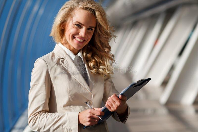 Mujer de negocios caucásica feliz que sostiene la carpeta Retrato en el edificio de oficinas fotografía de archivo
