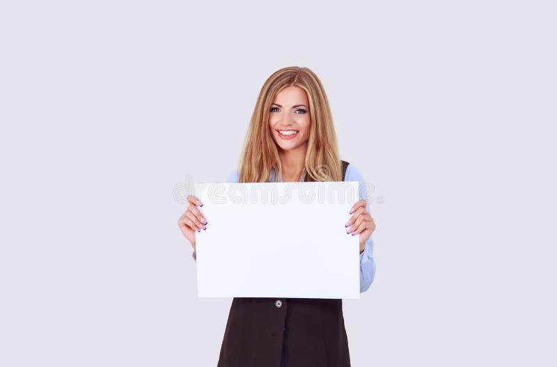 Mujer de negocios chica feliz sosteniendo una hoja de papel A3 limpia Escriba su texto, anuncie sus servicios púrpura claro aisla imagenes de archivo