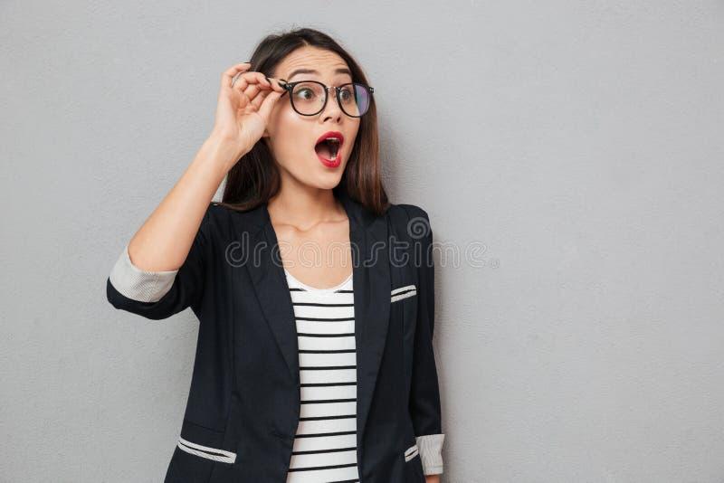 Mujer de negocios chocada en las lentes que miran lejos con la boca abierta foto de archivo