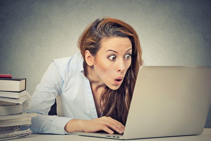 Mujer de negocios chocada que se sienta delante del ordenador portátil imagen de archivo