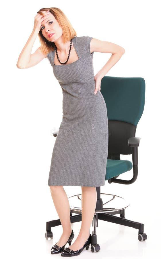 Mujer de negocios con dolor de espalda después del trabajo largo sobre silla   fotos de archivo