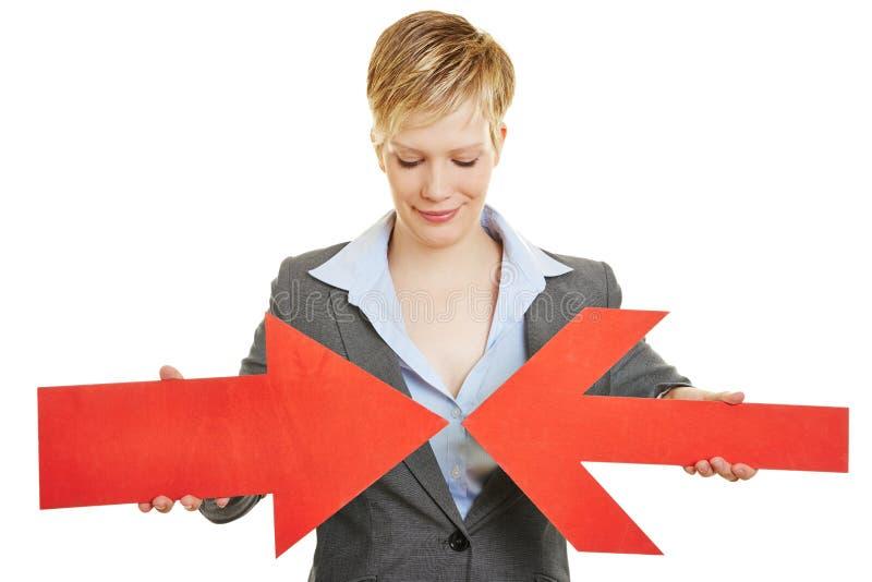 Mujer de negocios con dos flechas convergentes imágenes de archivo libres de regalías