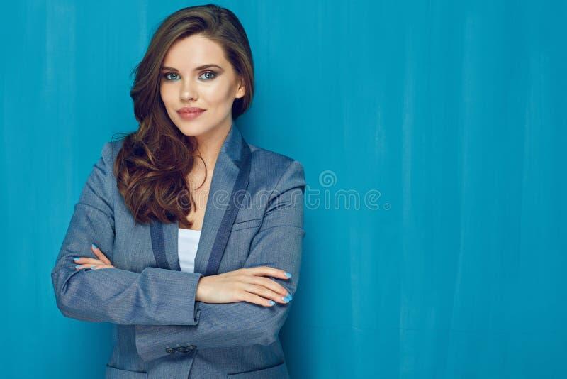 Mujer de negocios con el pelo largo que se opone a la pared azul fotografía de archivo libre de regalías