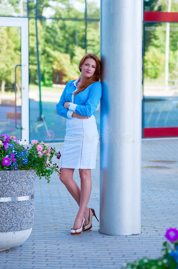 Mujer de negocios con el pelo rojo delante del edificio de oficinas. imágenes de archivo libres de regalías