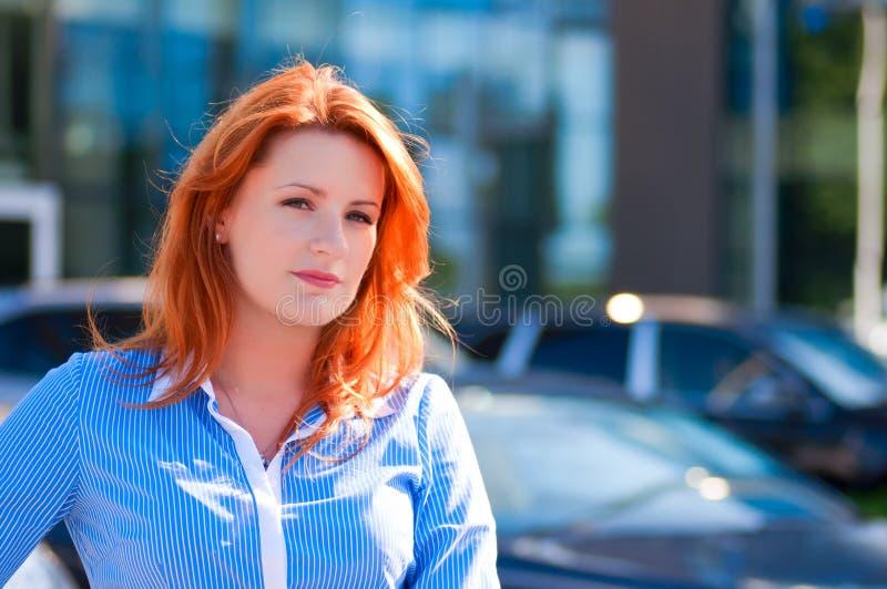 Mujer de negocios con el pelo rojo delante del edificio de oficinas. imagen de archivo