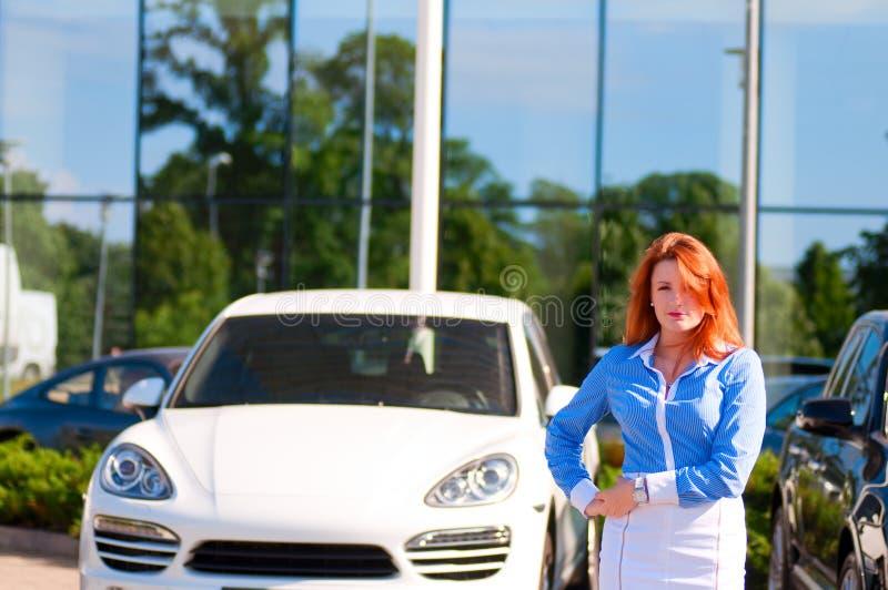 Mujer de negocios con el pelo rojo delante del edificio de oficinas. fotografía de archivo