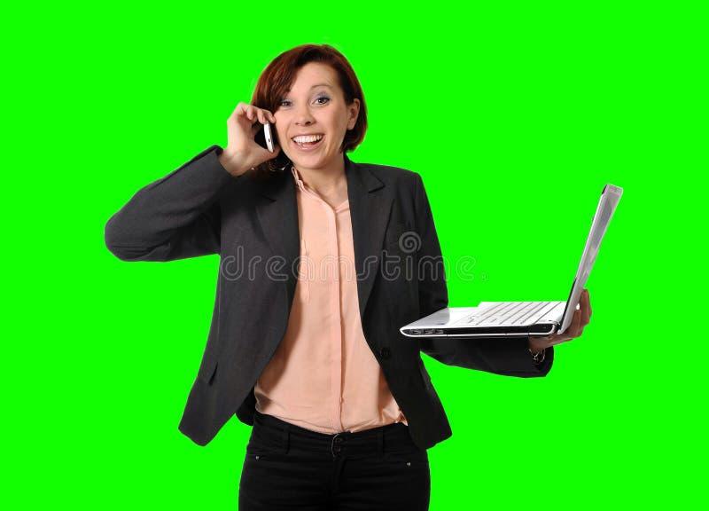 Mujer de negocios con el pelo rojo que habla en el teléfono celular móvil que sostiene disponible del ordenador portátil aislado  imagenes de archivo