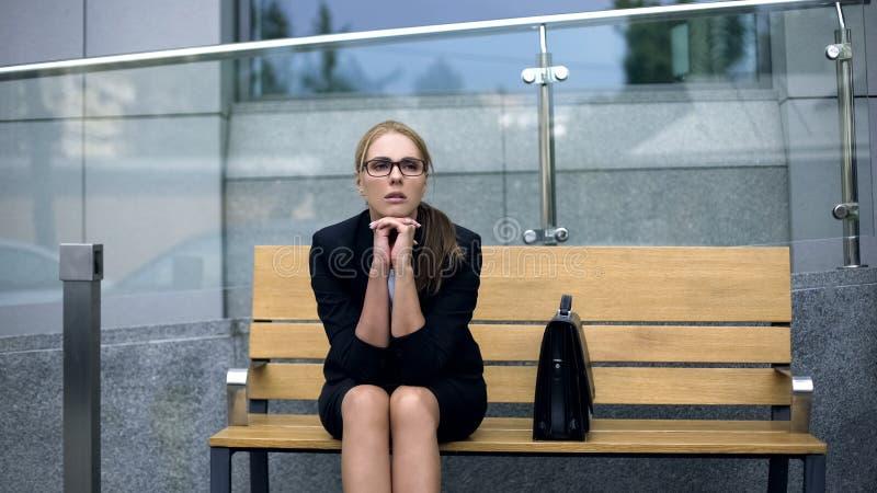 Mujer de negocios con exceso de trabajo que se sienta en banco cerca de la oficina, día laborable de agotamiento fotos de archivo