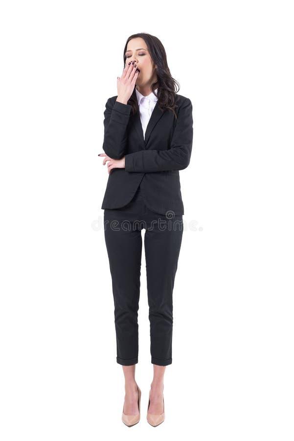 Mujer de negocios con exceso de trabajo soñolienta cansada en el traje negro que bosteza con los ojos cerrados imagen de archivo