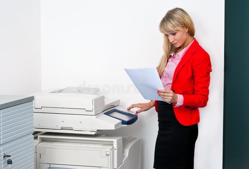 Mujer de negocios con los documentos que se colocan al lado de la impresora fotos de archivo libres de regalías