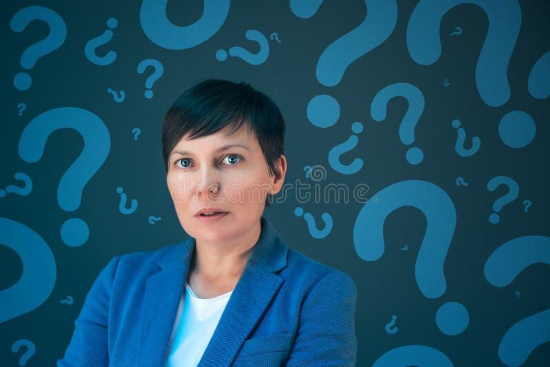 Mujer de negocios con los signos de interrogación que buscan respuestas imagen de archivo
