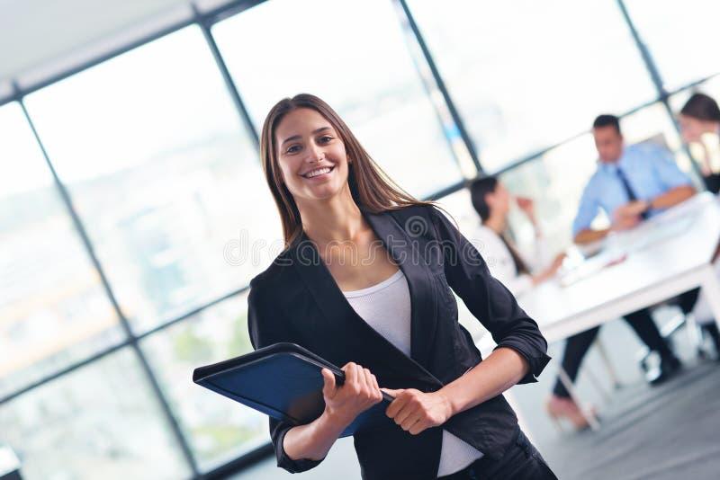 Mujer de negocios con su personal en fondo en la oficina imágenes de archivo libres de regalías