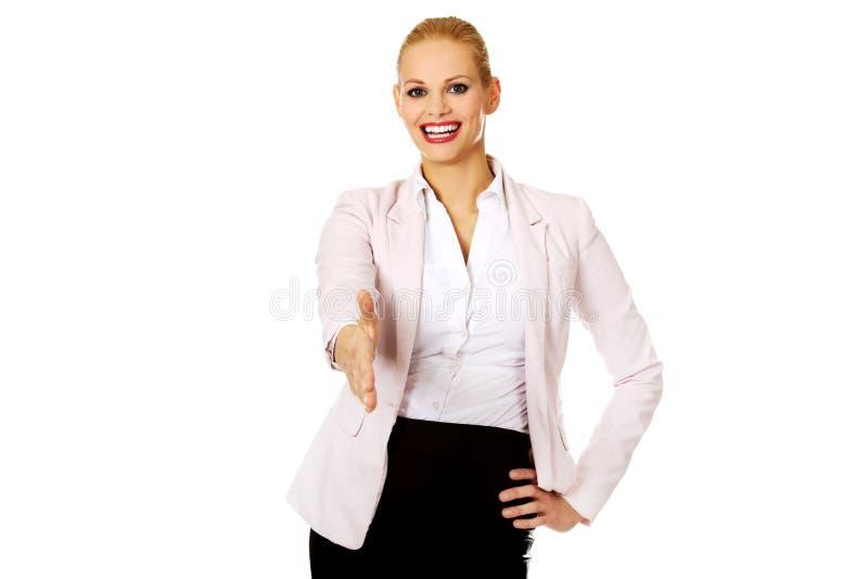 Mujer de negocios con una mano abierta lista para el apretón de manos imagen de archivo