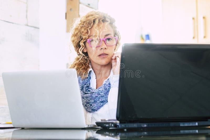 Mujer de negocios concentrada en el trabajo sobre el workstationwith ordenador portátil personal dos que mira la pantalla - andjo fotos de archivo