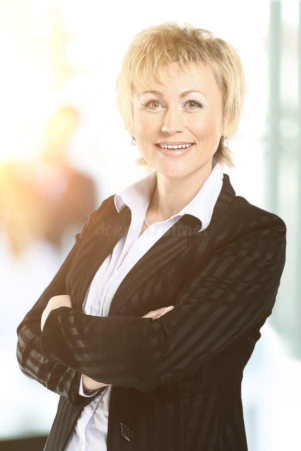 Mujer de negocios confiada en la oficina con un equipo detrás de ella foto de archivo